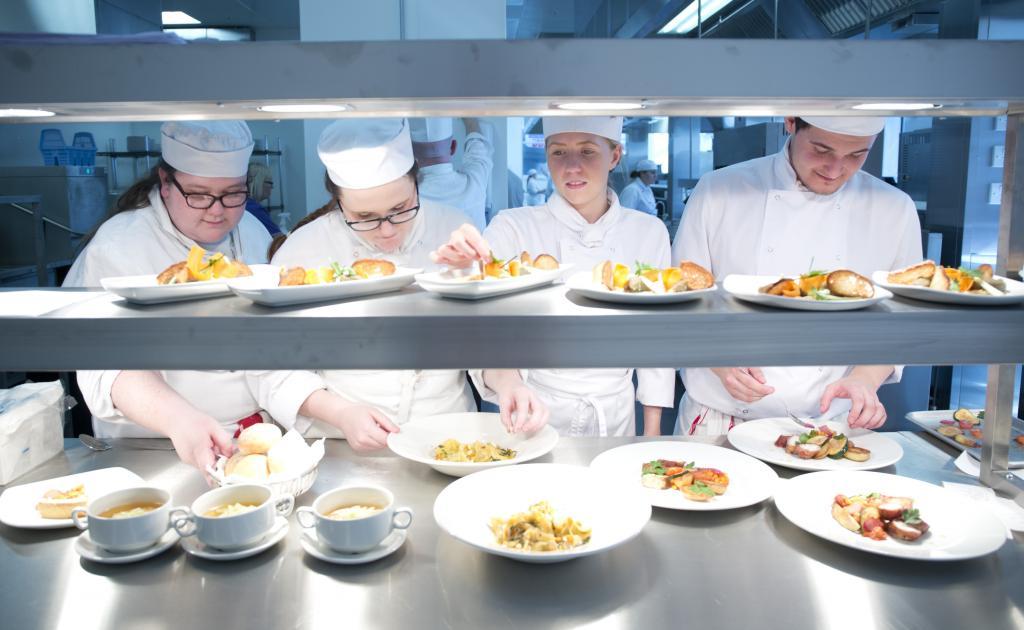 Student preparing lunch in the kitchen at Scholars Training Restaurant.
