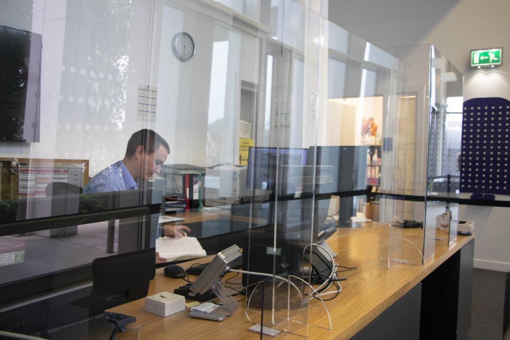 Photograph of staff member at reception behind protective screens