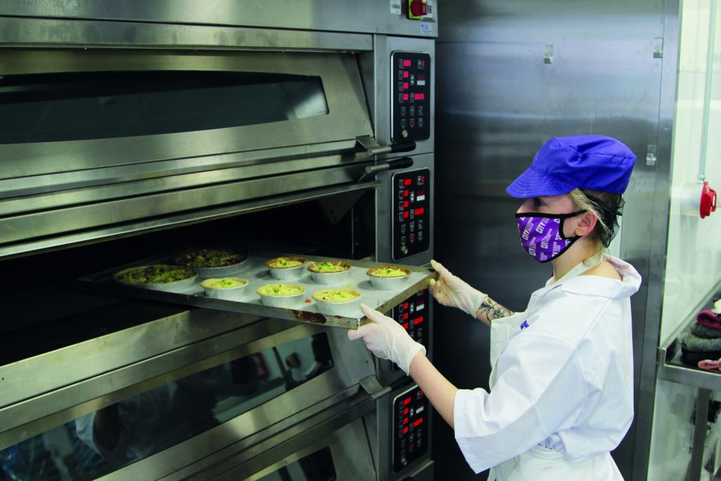 Photograph of culinary student with face mask in college campus kitchen