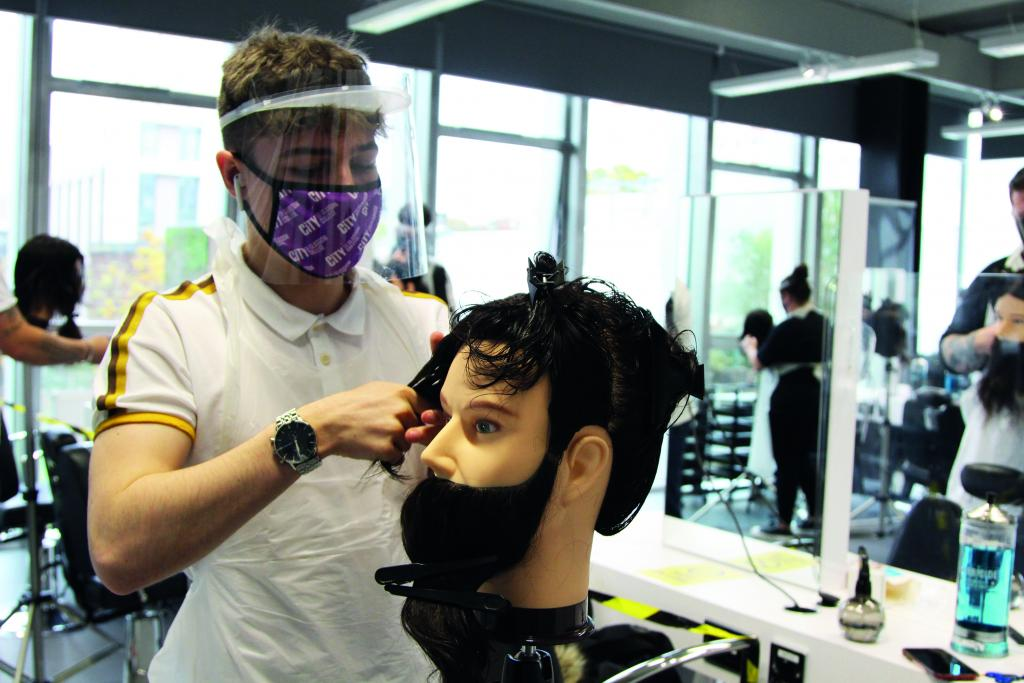 Photograph of hairdressing student wearing a face mask while practising on a model