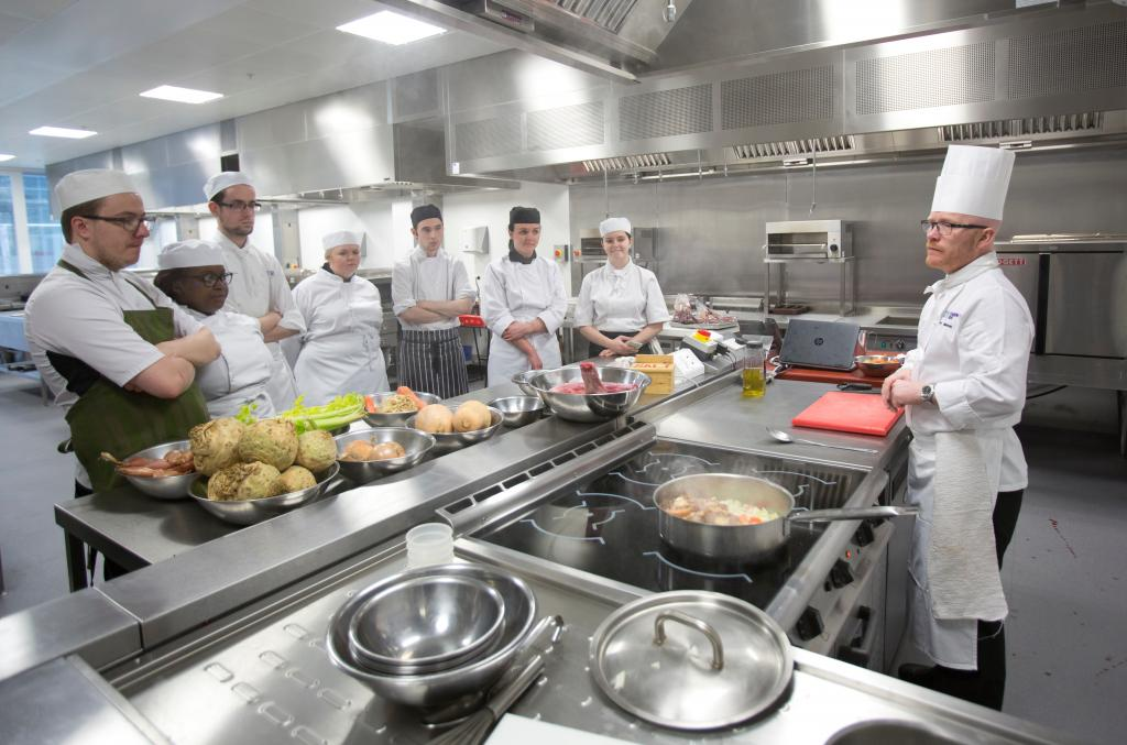 Photograph of Executive Chef Gary Maclean with students in college kitchen (photo taken pre-Covid)