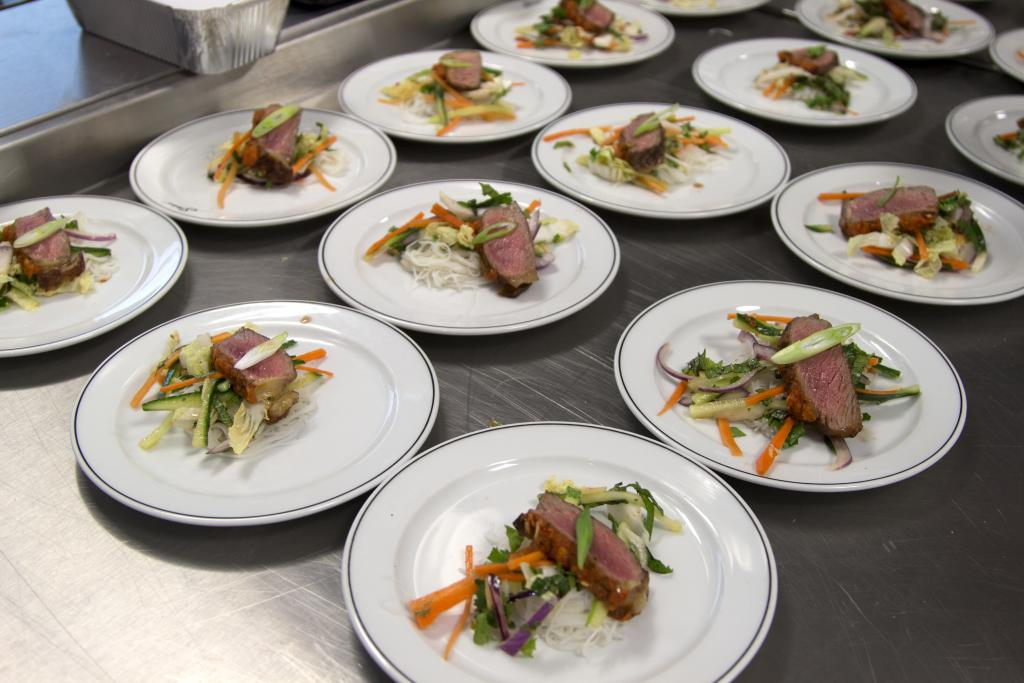 Dinner plates on the pass cooked by professional cookery students