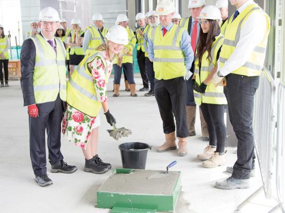 Senior civil servant Aileen McKechnie, the Scottish Government's director of advanced learning adding the final shovels of concrete to our Campus foundations