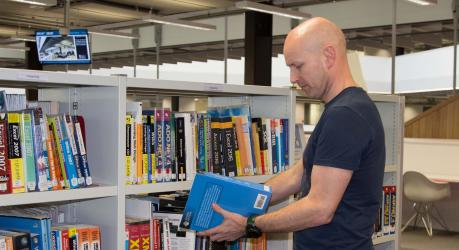 Student browsing books in Library at City campus.