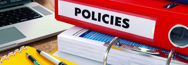 Policies folders, notebook and pen on a desk.