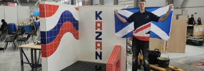 Worldskills tiling student holding saltire in front of his finished display.