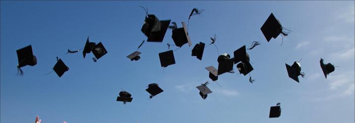 Alumni Association Graduation hats in the air